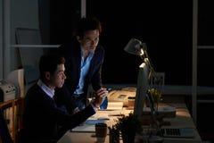 Hombres de negocios asiáticos que trabajan en oficina oscura foto de archivo libre de regalías