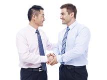 Hombres de negocios asiáticos y caucásicos que sacuden las manos Imágenes de archivo libres de regalías