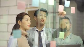 Hombres de negocios asiáticos que se encuentran en oficina almacen de video