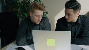 Hombres de negocios atractivos jovenes que hablan de proyecto de inicio en espacio de trabajo con el ordenador portátil almacen de video