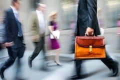 Hombres de negocios borrosos movimiento que caminan en la calle foto de archivo