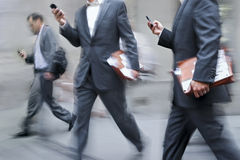 Hombres de negocios borrosos movimiento que caminan en la calle imágenes de archivo libres de regalías