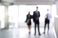Hombres de negocios borrosos que se colocan en pasillo del edificio Imagen de archivo