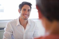 Hombres de negocios casuales que hablan en el escritorio y la sonrisa Fotografía de archivo