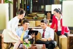 Hombres de negocios chinos asiáticos que se encuentran en pasillo del hotel Fotografía de archivo