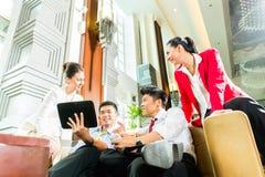 Hombres de negocios chinos asiáticos que se encuentran en pasillo del hotel Foto de archivo libre de regalías