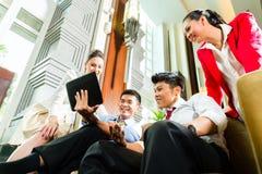 Hombres de negocios chinos asiáticos que se encuentran en pasillo del hotel Fotografía de archivo libre de regalías