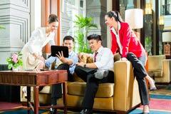 Hombres de negocios chinos asiáticos que se encuentran en pasillo del hotel Imagen de archivo libre de regalías