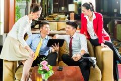 Hombres de negocios chinos asiáticos que se encuentran en pasillo del hotel Foto de archivo