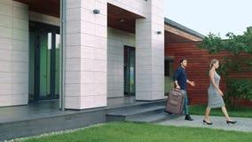 Hombres de negocios con el equipaje que sale de la casa de lujo almacen de metraje de vídeo
