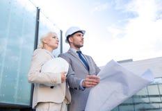 Hombres de negocios con el modelo y los cascos Imagen de archivo libre de regalías