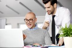 Hombres de negocios con la computadora portátil Imagen de archivo libre de regalías
