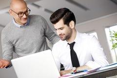 Hombres de negocios con la computadora portátil Imágenes de archivo libres de regalías