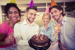 Hombres de negocios con la torta de cumpleaños que disfrutan del partido Foto de archivo