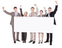 Hombres de negocios con los brazos aumentados sosteniendo la cartelera en blanco Fotos de archivo