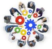 Hombres de negocios con los engranajes y concepto del trabajo en equipo Imagen de archivo libre de regalías