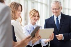 Hombres de negocios con los ordenadores de la PC de la tableta en la oficina fotografía de archivo libre de regalías