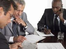 Hombres de negocios con papeleo en la mesa de reuniones Fotografía de archivo