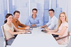 Hombres de negocios confiados en la mesa de reuniones en oficina Foto de archivo