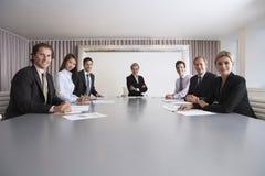 Hombres de negocios confiados en la sala de conferencias imagen de archivo