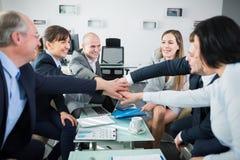 Hombres de negocios confiados que apilan las manos durante la reunión Fotografía de archivo