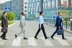 Hombres de negocios confiados que cruzan el camino Imagen de archivo