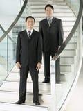 Hombres de negocios confiados que se colocan en las escaleras Fotos de archivo