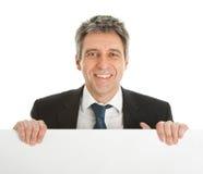 Hombres de negocios confidentes que presentan a la tarjeta vacía Imagen de archivo
