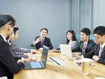 Hombres de negocios corporativos asiáticos que se encuentran en oficina foto de archivo