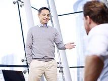 Hombres de negocios corporativos que charlan en oficina Imagen de archivo