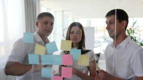 Hombres de negocios creativos con muchas notas pegajosas a la ventana en la sala de reunión metrajes