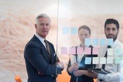 Hombres de negocios creativos jovenes con el CEO mayor Fotos de archivo
