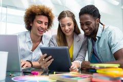 Hombres de negocios creativos que miran la tableta digital Fotos de archivo libres de regalías