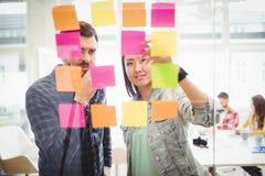 Hombres de negocios creativos que miran notas pegajosas coloreadas multi sobre el vidrio imagen de archivo libre de regalías