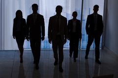 Hombres de negocios de la silueta que caminan en oficina Fotografía de archivo libre de regalías