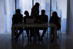 Hombres de negocios de la silueta que discuten en oficina Fotos de archivo