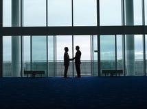 Hombres de negocios de la silueta que sacuden las manos en el aeropuerto Imagen de archivo libre de regalías