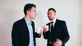 Hombres de negocios de la taza de consumición de café en la sala de reunión metrajes
