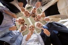 Hombres de negocios de los pulgares que nievan para arriba en la oficina Imagen de archivo