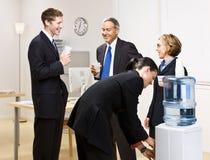 Hombres de negocios del agua potable en el refrigerador de agua