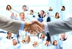 Hombres de negocios del apretón de manos con el equipo de la compañía Foto de archivo libre de regalías