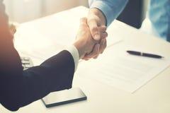 Hombres de negocios del apretón de manos después de firmar del contrato de sociedad