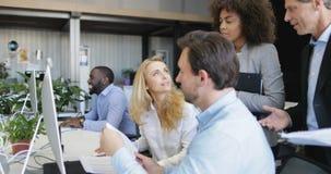 Hombres de negocios del grupo de la estrategia de los disscuss que señala en el monitor de computadora que trabaja junto en espac almacen de metraje de vídeo