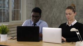 Hombres de negocios del hombre y mujer que trabajan en los ordenadores portátiles almacen de video