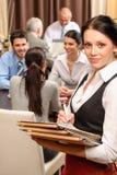 Hombres de negocios del menú del asimiento de la camarera en el restaurante Imagen de archivo