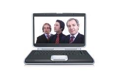 Hombres de negocios dentro de una pantalla negra de la computadora portátil Foto de archivo libre de regalías