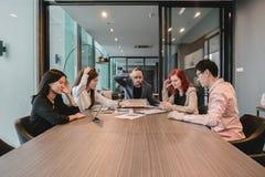 Hombres de negocios deprimidos en sala de reunión, teniendo problemas en el co Foto de archivo libre de regalías
