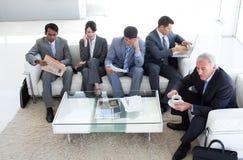 Hombres de negocios diversos en una sala de espera Foto de archivo libre de regalías