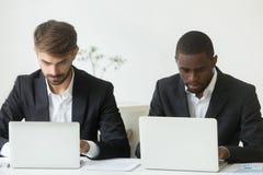 Hombres de negocios diversos ocupados enfocados que trabajan en los ordenadores portátiles que comparten offi fotografía de archivo