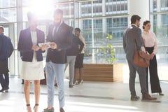 Hombres de negocios diversos que miran y que discuten sobre la tableta digital en oficina del pasillo fotos de archivo libres de regalías